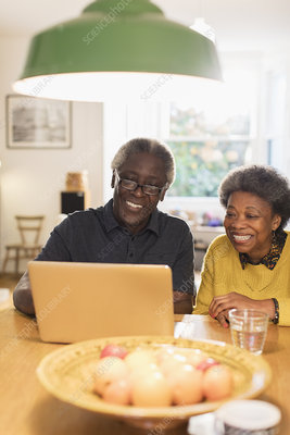 Happy senior couple using laptop in kitchen
