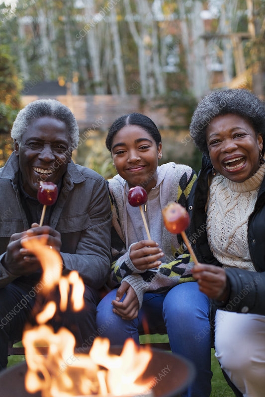 Family enjoying candy apples at campfire