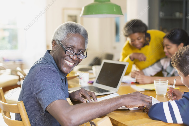 Portrait smiling, senior man using laptop with family