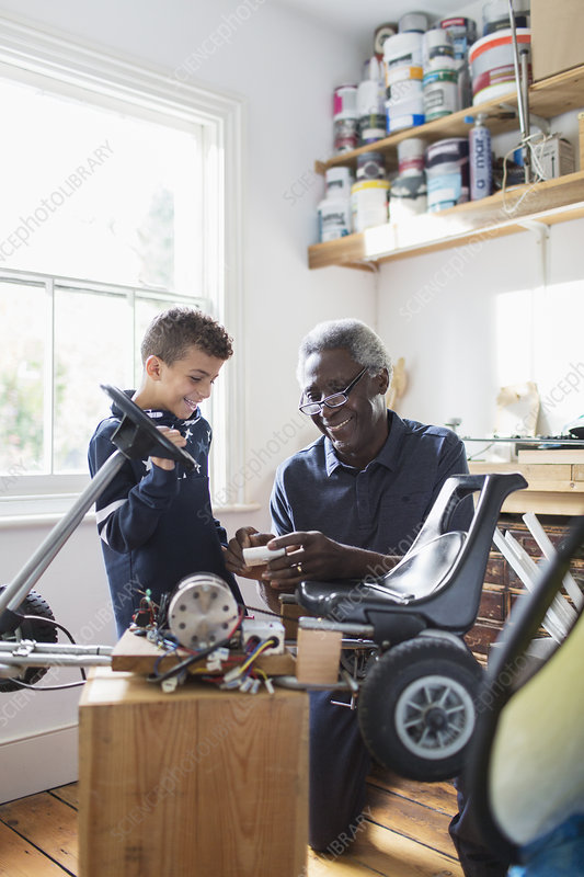 Grandfather and grandson assembling go-cart in garage