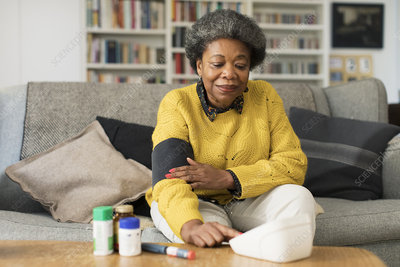 Senior woman checking blood pressure in living room