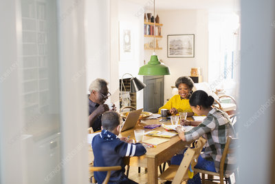 Grandparents with grandchildren doing homework,