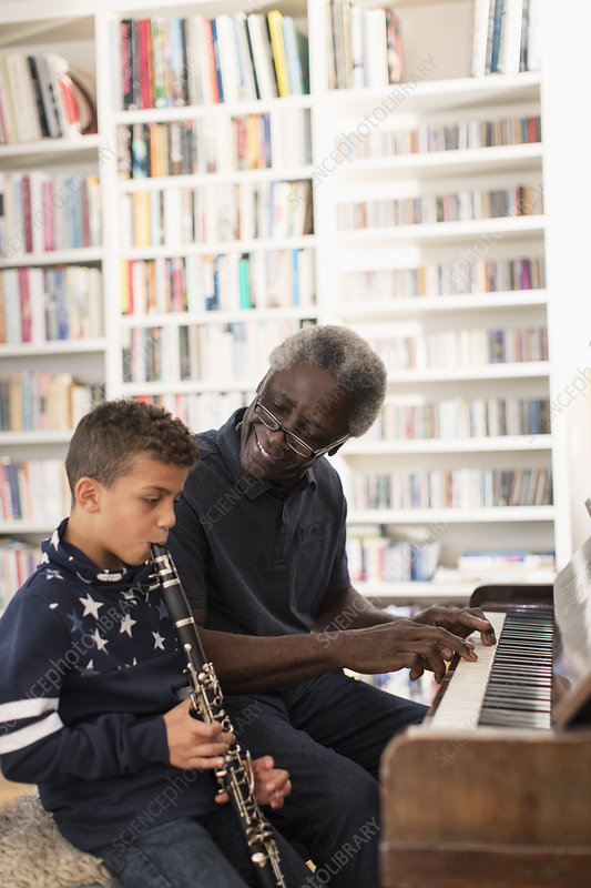 Grandfather and grandson playing piano and clarinet