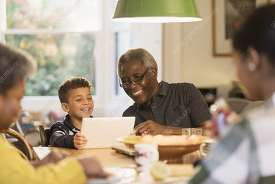 Smiling grandfather and grandson using digital tablet