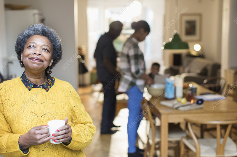 Senior woman drinking coffee with family in background