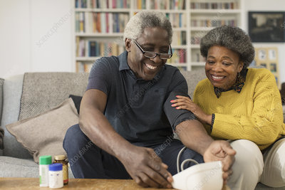 Smiling senior couple checking blood pressure