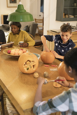 Family carving Halloween pumpkins at dining table