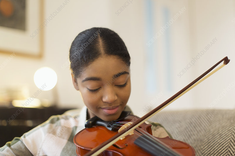 Focused teenage girl playing violin