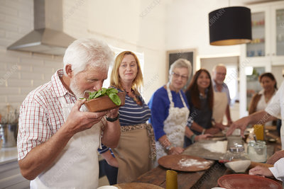 Active senior friends taking cooking class