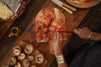 Overhead view woman slicing fresh tomatoes for pizza