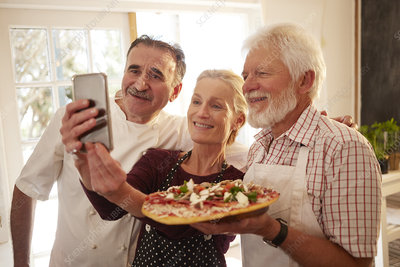 Chef and senior couple taking selfie with pizza