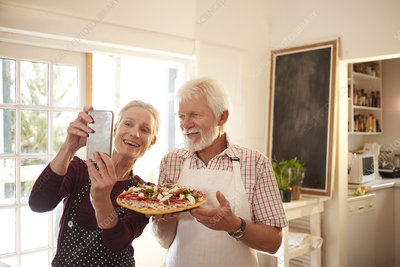 senior couple taking selfie with pizza at cooking class