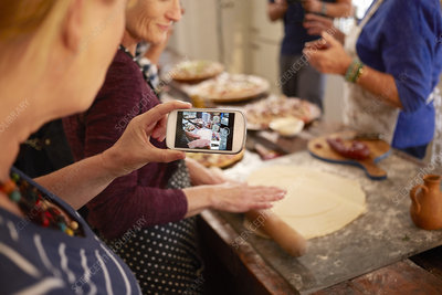 Woman photographing friend making pizza dough