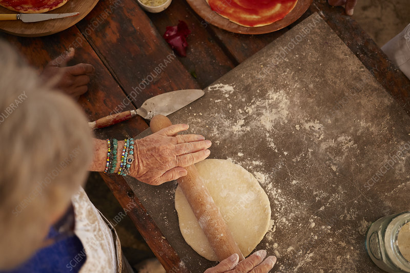 Overhead view senior woman rolling pizza dough