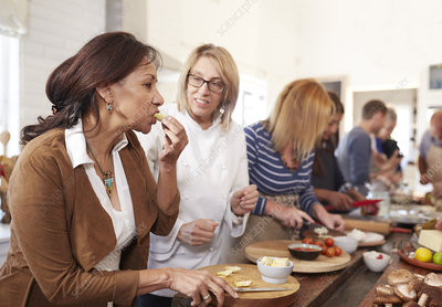 Senior woman and chef tasting cheese