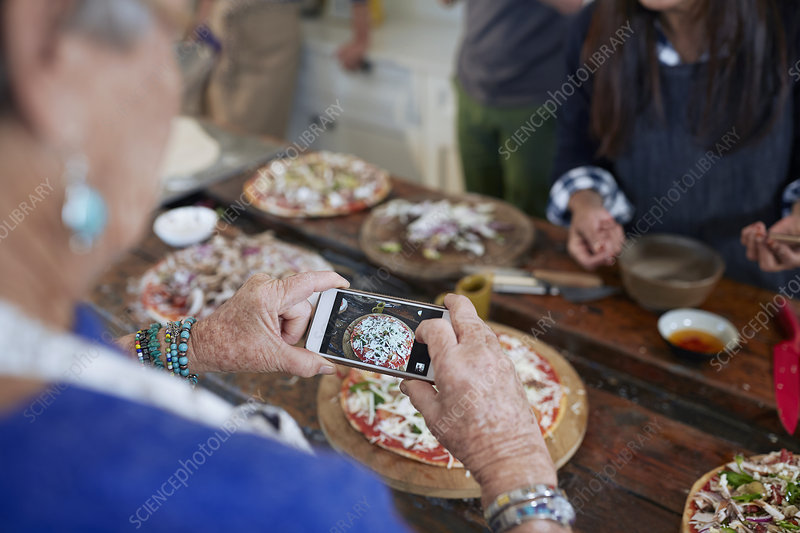 Senior woman photographing homemade pizza