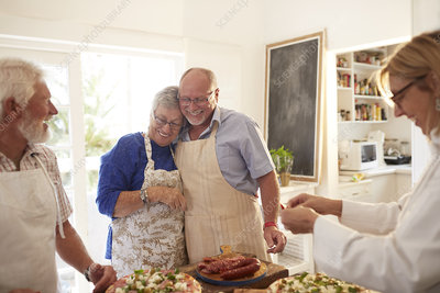 Affectionate senior couple enjoying pizza cooking class