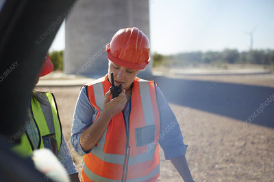 Female worker using walkie-talkie at power plant
