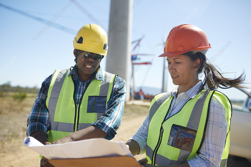 Engineers reviewing blueprints at power plant