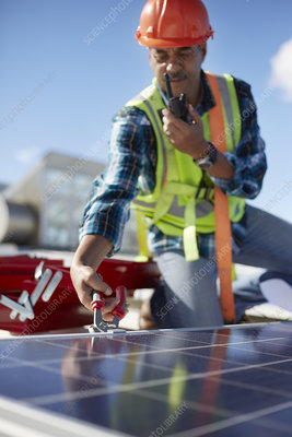 Male engineer with walkie-talkie repairing solar panel