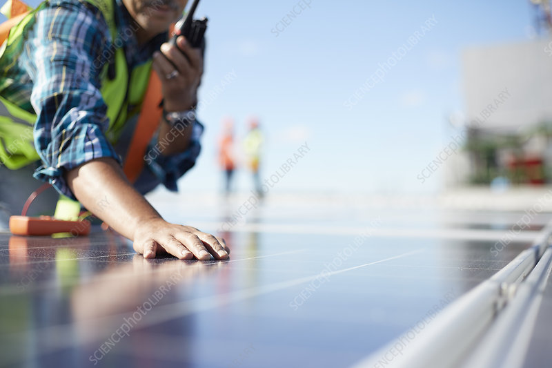 Engineer with walkie-talkie inspecting solar panels