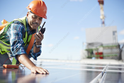 Engineer with walkie-talkie inspecting solar panel