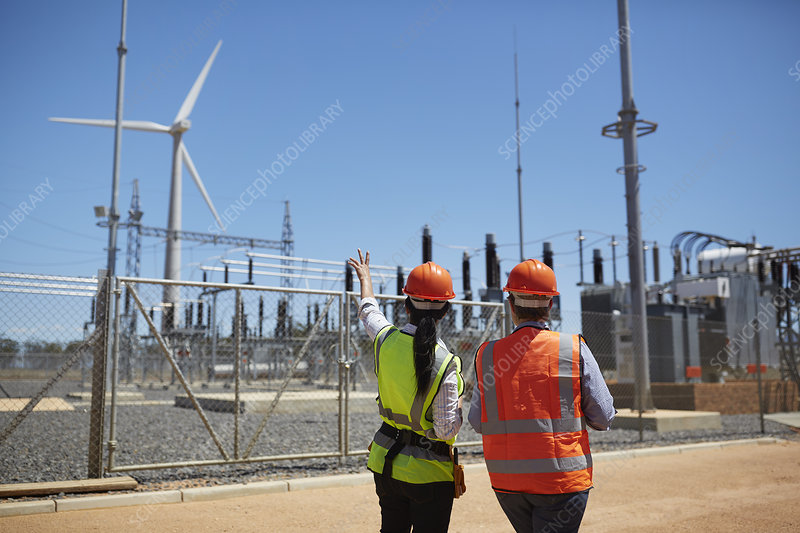Workers watching wind turbine at power plant
