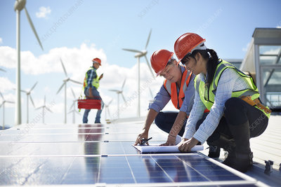 Engineers reviewing blueprints at solar panel