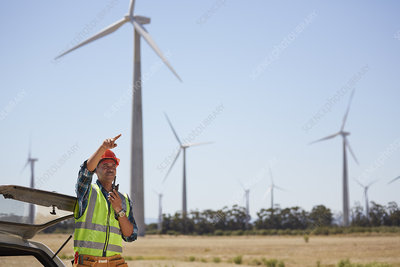 Engineer with walkie-talkie at wind turbine power plant