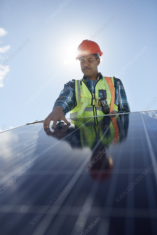 Engineer examining solar panel at sunny power plant