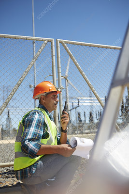 Engineer with walkie-talkie at sunny power plant