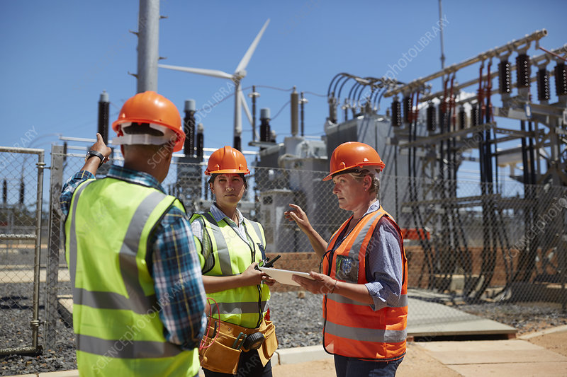 Engineers with digital tablet at sunny power plant