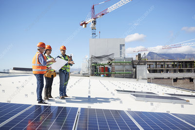 Engineers with blueprint at solar panels