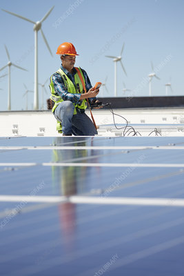Engineer with equipment inspecting solar panels