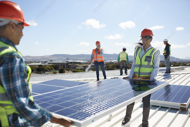 Engineers lifting solar panel at sunny power plant