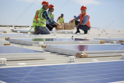 Engineers installing solar panels at sunny power plant