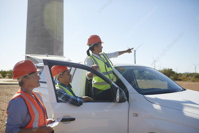 Engineers at truck at sunny wind turbine power plant