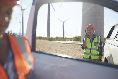 Smiling engineer using walkie-talkie at truck