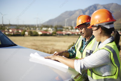 Engineers reviewing blueprints at truck