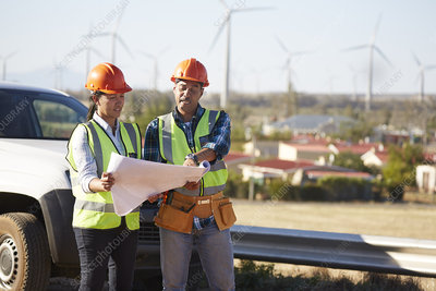 Engineers reviewing blueprints near wind turbine farm