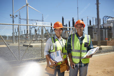 Portrait engineers with clipboards at power plant