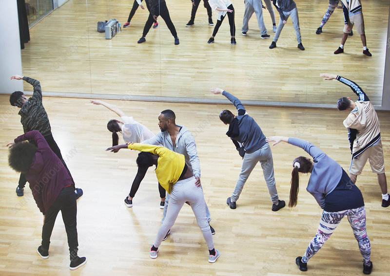 Instructor guiding students in dance class studio