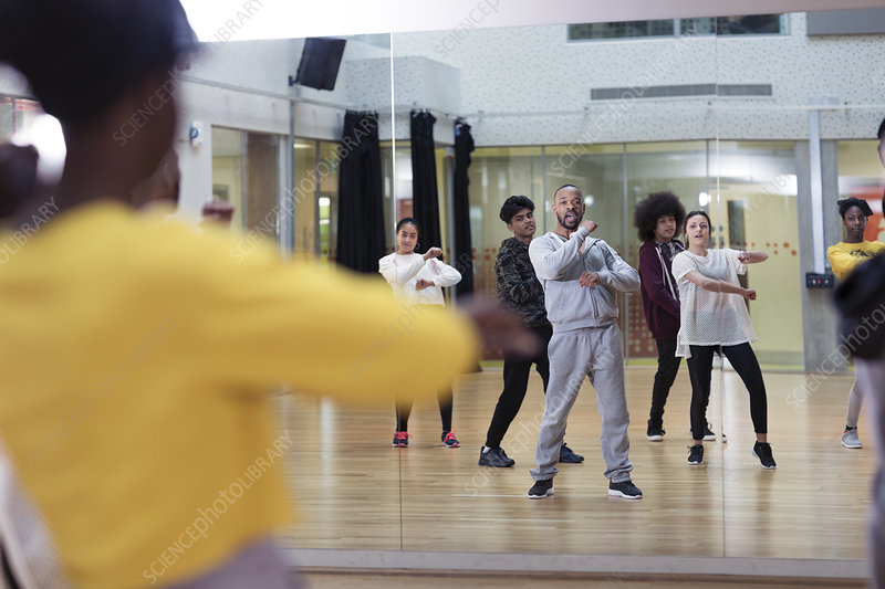 Male instructor leading dance class in studio mirror
