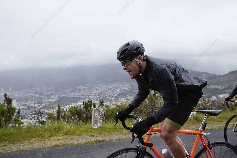 Determined male cyclist cycling on rainy road