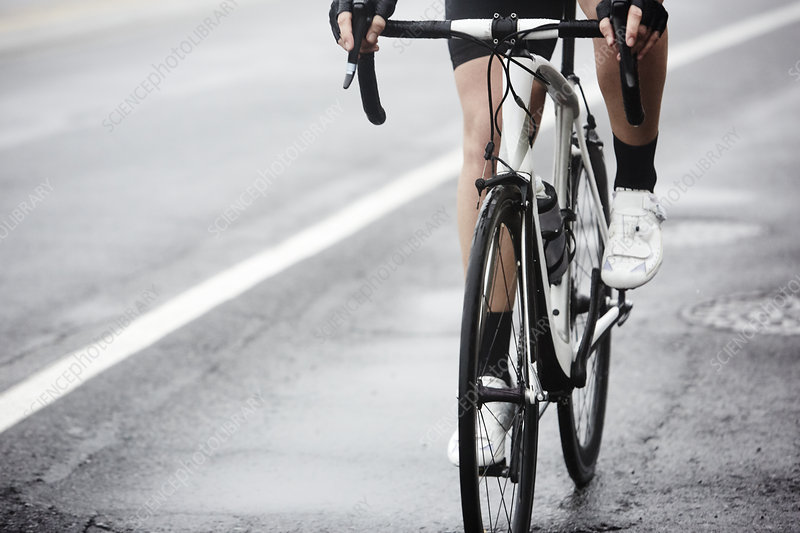 Cyclist cycling on wet road