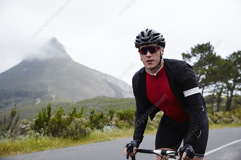 Portrait confident, determined cyclist cycling on road