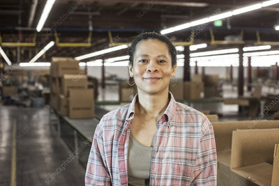 Portrait of worker in warehouse with product stored in boxes