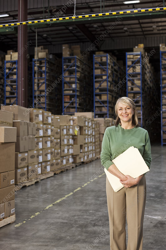 Portrait of executive in warehouse with cardboard boxes