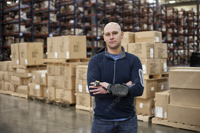 Portrait of worker in warehouse, showing products in boxes