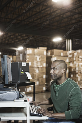 Worker working on computer in warehouse with boxes in back